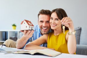 Happy couple holding keys to new home and miniature house